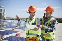 Engineers using walkie-talkie and digital tablet at solar power plant — Stock Photo