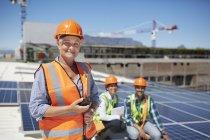 Улыбающаяся, уверенная в себе женщина-инженер с рацией на солнечной солнечной электростанции — стоковое фото