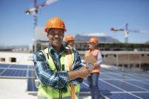 Portrait confident engineer installing solar panels on sunny rooftop — Stock Photo