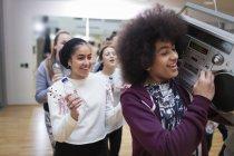 Cool teenage girls with boom box enjoying dance class in studio — Stock Photo