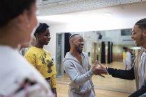 Энтузиасты-подростки, пожимающие руки в танцевальном классе в студии — стоковое фото
