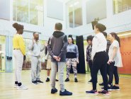 Teenage students listening to male instructor in dance class studio — Stock Photo