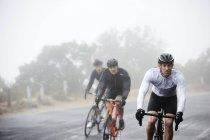 Выделенные мужской велосипедистов Велоспорт на дороге дождливым — стоковое фото