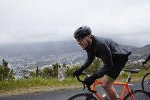 Визначено чоловічого велосипедиста їзда на велосипеді по дорозі, дощова — стокове фото
