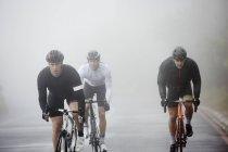 Cyclistes masculins dédiés cyclistes sur route pluvieuse — Photo de stock