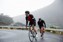 Dedicated male cyclists cycling on wet road — Stock Photo