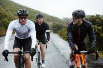 Ciclistas masculinos, ciclismo estrada molhada — Fotografia de Stock