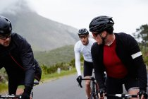 Male cyclist friends cycling at mountain road — Stock Photo