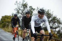 Smiling male cyclist cycling with friends — Stock Photo
