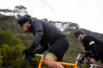Focused, determined male cyclist cycling uphill — Stock Photo