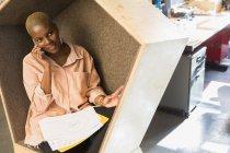 Empresaria creativa hablando por teléfono inteligente en cubículo - foto de stock