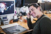 Retrato sonriente, confiado diseñador gráfico masculino trabajando en el escritorio — Stock Photo