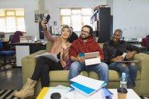 Glücklich kreative Geschäftsleute nehmen Selfie in lässigen Großraumbüro — Stockfoto