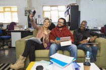 Happy creative business people taking selfie in casual open plan office — Stock Photo
