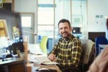 Ritratto sorridente, sicuro di sé creativo uomo d'affari che lavora nell'ufficio — Foto stock