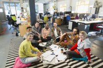 Portrait confident creative business team meeting, brainstorming in circle on office floor — Stock Photo