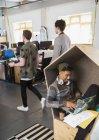 Homme d'affaires créatif avec écouteurs utilisant un ordinateur portable dans un cubby de bureau — Photo de stock