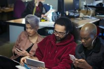 Empresarios creativos usando teléfonos inteligentes y tabletas digitales - foto de stock