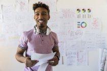 Портрет посміхаючись, впевненої творчої бізнесмен висить документи на стіні office — стокове фото