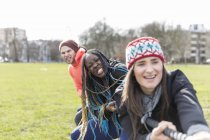 Determined team pulling rope in tug-of-war in park — Stock Photo