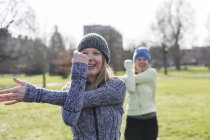 Усміхається жінка, вправи, розтягування руку в Сонячний парк — стокове фото