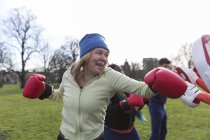 Determined senior woman boxing in green park — Stock Photo