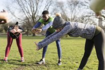 People exercising, stretching in sunny park — Stock Photo