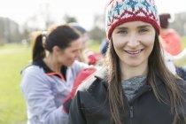 Портрет посміхаючись, впевнена в собі жінка, що здійснюють в парку — стокове фото