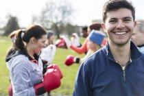 Ritratto sorridente, giovane sicuro boxe nel parco — Foto stock