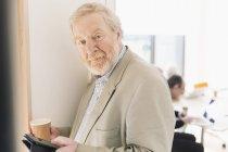 Портрет уверенный старший бизнесмен с цифровой планшет — стоковое фото