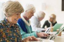 Femmes âgées utilisant des ordinateurs portables dans la salle de conférence réunion — Photo de stock