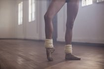 Junge weibliche Ballett-Tänzerin stretching Fuß im Tanzstudio — Stockfoto