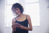 Sorridente giovane ballerina sms con smart phone in studio di danza — Foto stock