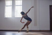 Graceful young female dancer practicing in dance studio — Stock Photo