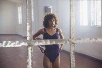 Сосредоточена на молодой танцовщице, стоящей перед зеркалом в танцевальной студии — стоковое фото