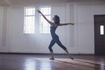 Грациозная молодая танцовщица, практикующая в танцевальной студии — стоковое фото