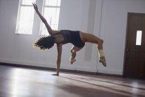 Graciosa, forte jovem bailarina feminina praticando no estúdio de dança — Fotografia de Stock