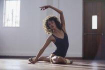 Grazioso giovane ballerina stretching in studio di danza — Foto stock