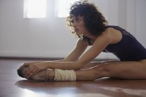 Focused young female dancer stretching legs in dance studio — Stock Photo