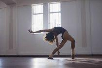 Изящная, гибкая молодая танцовщица, практикующая в танцевальной студии — стоковое фото