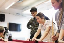 Teenagers playing pool in community center — Stock Photo