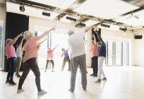 Активные старшеклассники танцуют, тренируются и растягиваются по кругу — стоковое фото