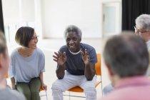 Sorridente uomo anziano parlando con il gruppo nel centro della comunità — Foto stock