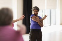Smiling active senior stretching arm in exercise class — Stock Photo