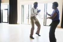 Juguetona pareja mayor activa bailando en estudio de baile - foto de stock