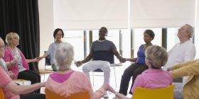 Serene active seniors holding hands, meditating in circle — Stock Photo