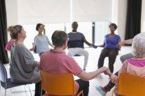 Heitere aktive Senioren Hand in Hand, meditieren im Kreis — Stockfoto