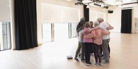 Personas mayores activas vinculándose, abrazándose en círculo en el estudio de ejercicios — Stock Photo