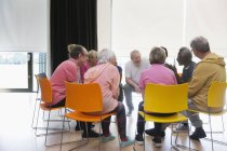 Active seniors talking in circle in community center — Stock Photo
