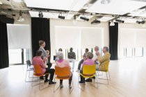 Active seniors clapping for instructor in circle in community center — Stock Photo